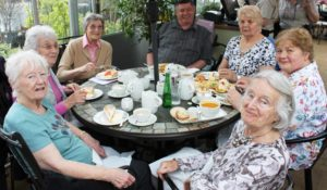 Photo of group of visually impaired adults enjoying tea and cake at a garden centre