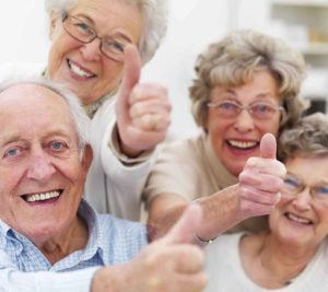 Image of group of older people holding their thumbs up